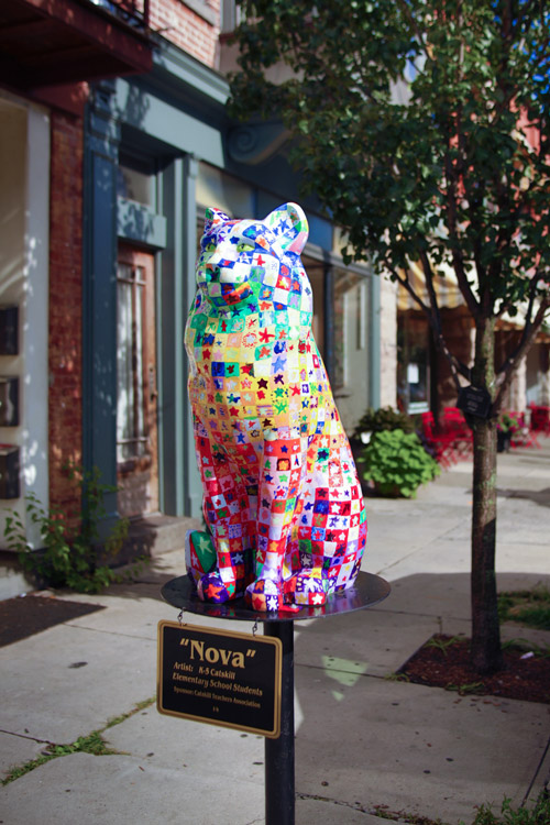 A brightly colored statue of a cat installed on a city sidewalk